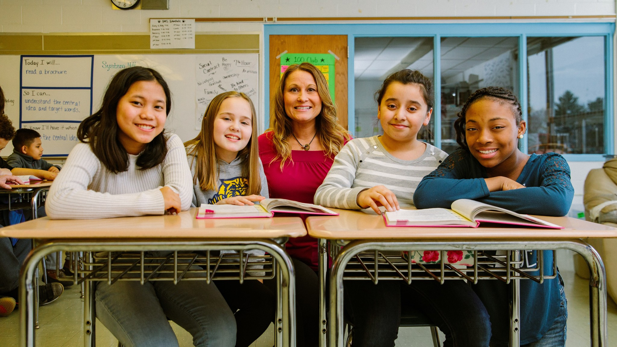 A middle school teacher and four students at their desks smiling